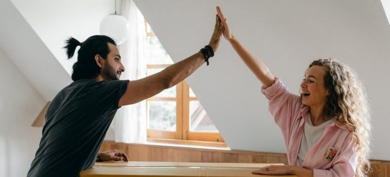 Two people high fiving and about to hire professionals for your local CA move